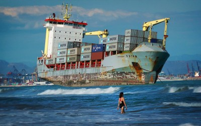 FREIGHTENED_Swimmers share the beach with a rusty container ship